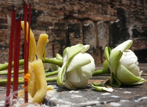Lotus flowers, candles and incense at a temple in Sukhothai, Thailand