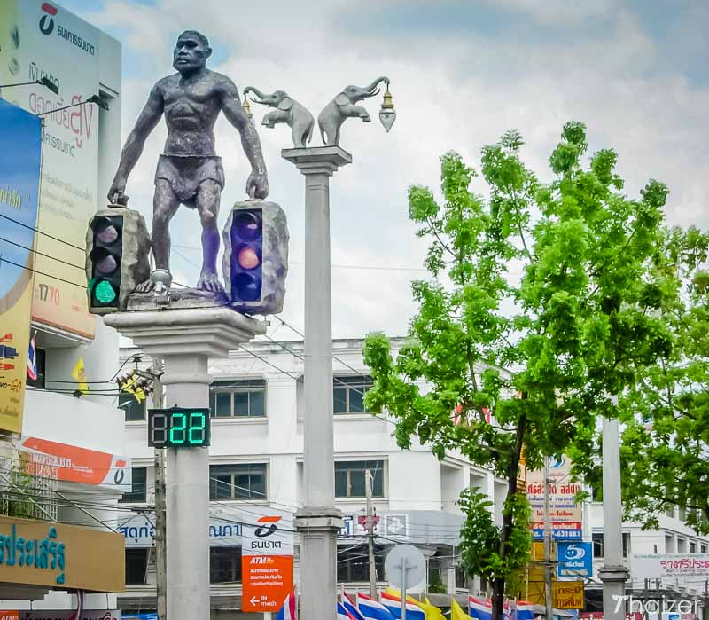 Caveman or Neanderthal man holding up traffic lights in Krabi Town