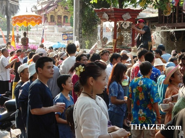 crowds gather to pour water over Buddha images as they are paraded through the streets during the Songkran Festival