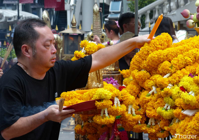 making an offering at the Erawan Shrine, Bangkok