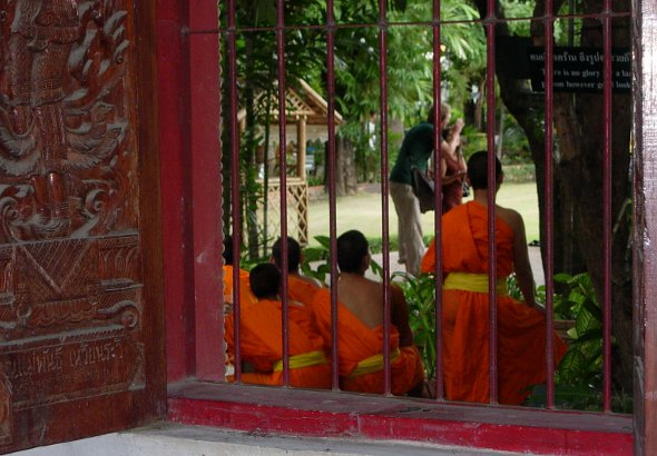 Novice monks watching tourists at Wat Phra Singh in Chiang Mai