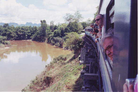 Tourists peering out of the train window on the Death Railway, Kanchanaburi