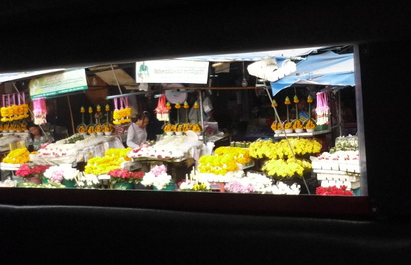 Roadside flower market viewed through the side window of a moving songthaew