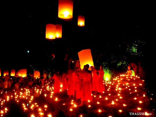 Novice monks surrounded by candles release sky lanterns during Loy Krathong Festival