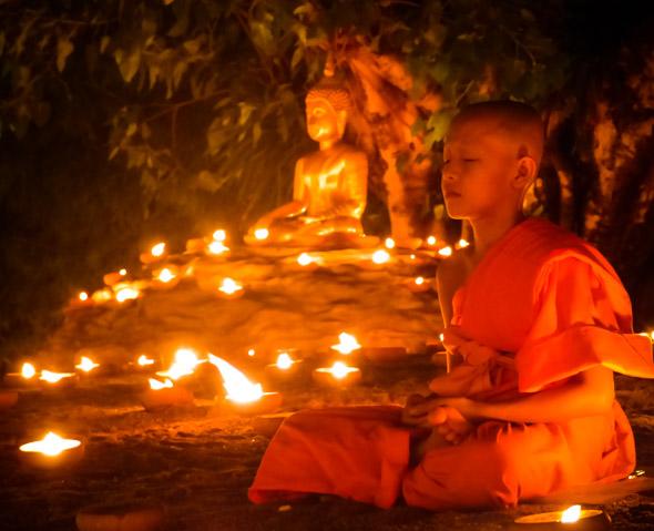 Novice Thai monk meditates at Wat Pan Tao, Chiang Mai